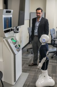 Dr. Elkins facilitates an interaction between robots Pepper and AVATAR.